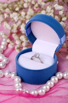 Обручальное кольцо на розовой ткани