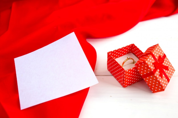 Engagement ring in a red box on a white wooden background. declaration of love on valentine's day