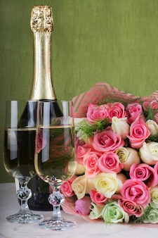 Обручальное кольцо с бриллиантом в бокале шампанского и большой букет роз