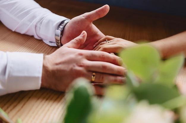 Обручальное кольцо с камнем на нежной руке невесты