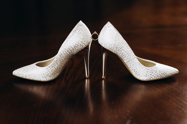 Engagement ring with gemstone is located between the bridal heels