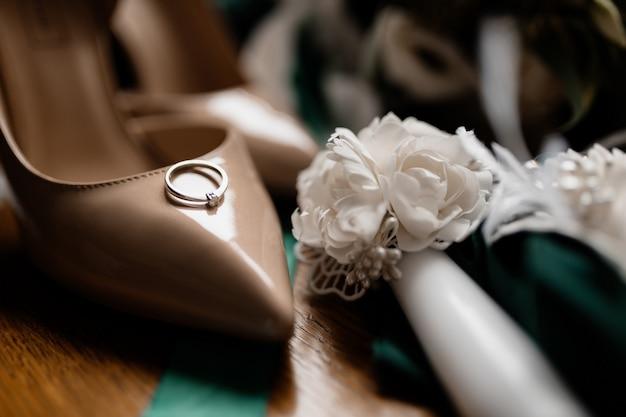 Обручальное кольцо с драгоценным камнем лежит на свадебной обуви