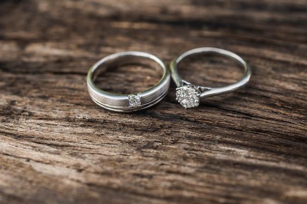 婚約指輪、木製の背景にカップルのための結婚指輪。結婚式、豪華な婚約ダイヤモンドリングジュエリー
