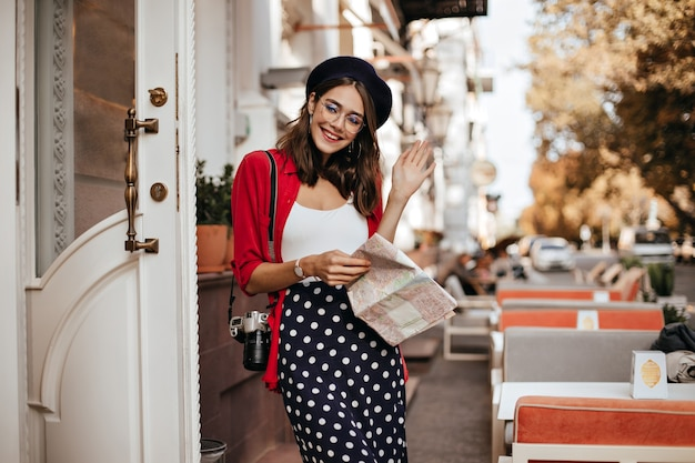 Привлекательная молодая леди с волосами брюнетки и берет во французском стиле, камера на плече, держит карту и улыбается на террасе кафе у стены осеннего города