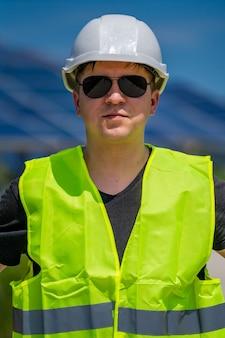 Инженер в солнцезащитных очках и шлеме на фоне электростанции солнечной энергии.