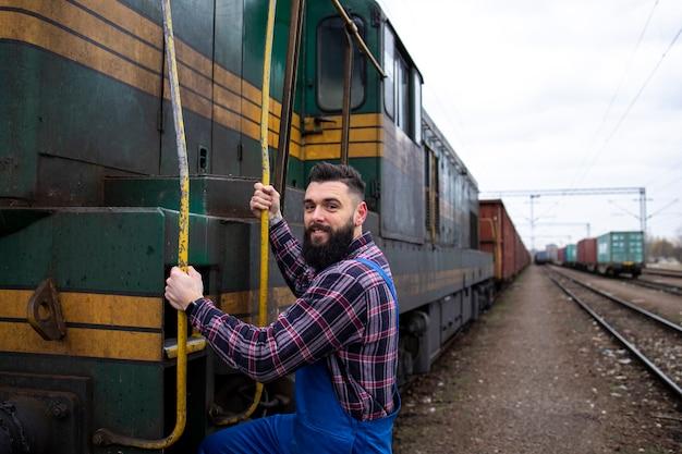 Машинист садится на поезд для перевозки груза к месту назначения.