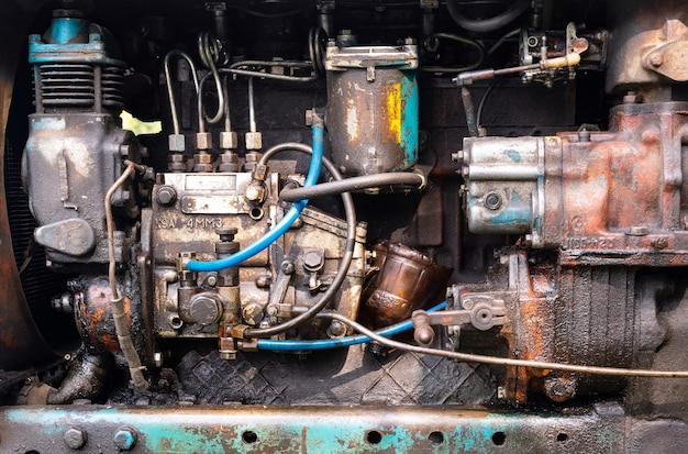 The engine from an old tractor is stained with engine oil and grease