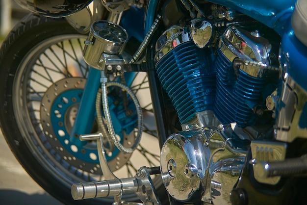 カラフルなカスタムブルーモーターサイクルのエンジン。きらびやかなクロームが特徴で、情熱がディテールにつながることを象徴しています。