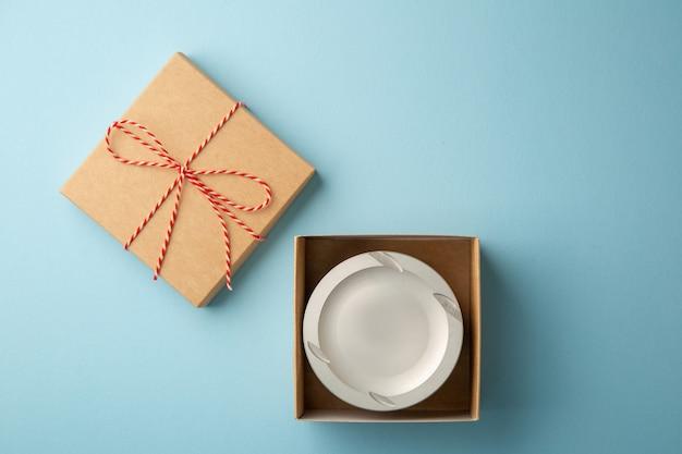 파란색 배경, 선물 개념, 복사 공간에 있는 선물 상자 내부의 엔진 피스톤
