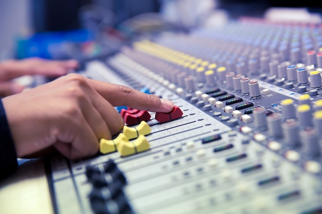 Single microphone with headphones on sound mixer board in