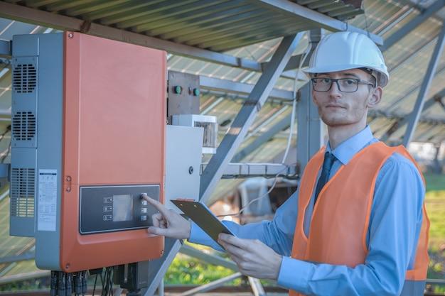 엔지니어, 제복을 입은 남자가 태양 광 발전소의 제어 시스템을 확인합니다.