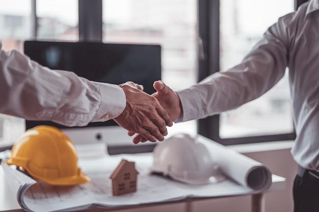 エンジニアと建築家の建設労働者がオフィスでチームワークのために働いている間握手します。