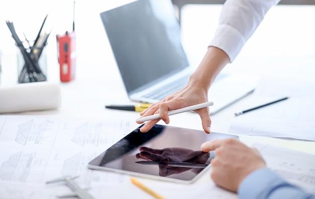 Инженер и команда архитекторов используют планшет и компьютер для планирования и обсуждения строительства здания