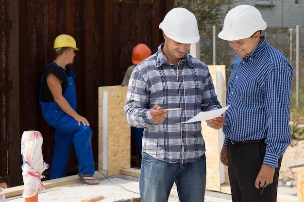 ヘルメットをかぶったエンジニアと建築家が、建設現場での事務処理について、背後で作業している建設業者と話し合っています。
