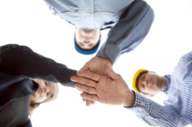 Инженер и архитекторы складывают руки вместе для нового проекта.