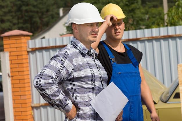 現場のエンジニアと建築請負業者がヘルメットをかぶって一緒に立って、ドキュメントを持っている間、右側のフレームから誰かを見ています。