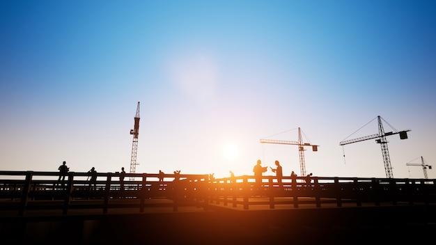 エンジニアと建設作業員とシルエットクレーンの3dレンダリング