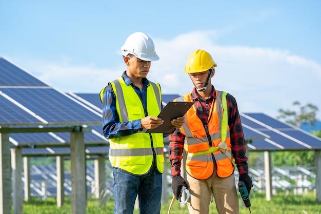 Инженер и электрик осматривают солнечную панель на солнечной электростанции, инженер работает над заменой солнечной панели.