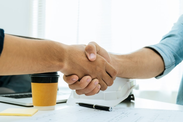 Engineer, architect, construction worker team hands shaking after plan project contract on workplace desk in meeting room office at construction site, contractor, partnership, construction concept
