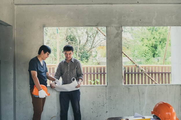 Engineer and architect discussing about project in building construction site.