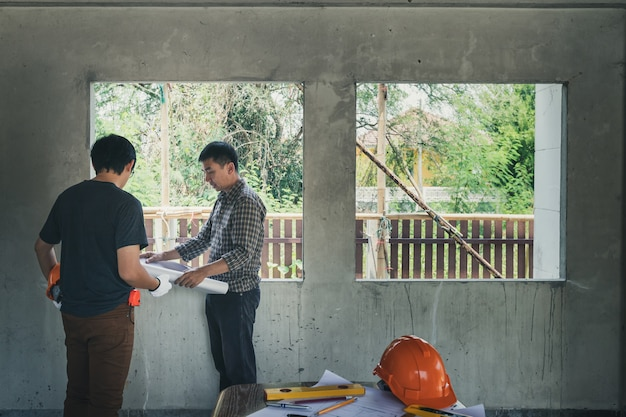 Engineer and architect discussing in building construction site.