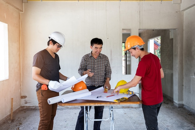 Engineer and architect discussing with foreman about project in construction site