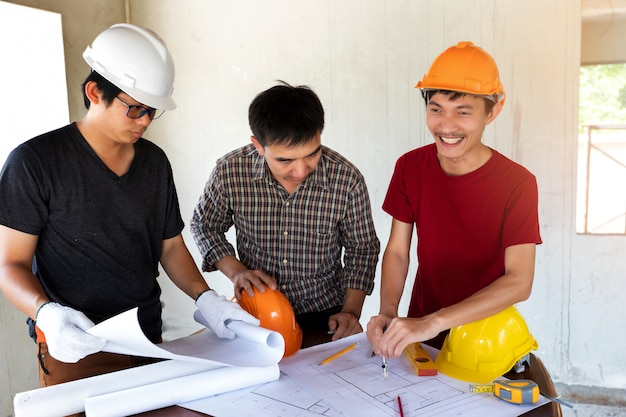 Engineer and architect discussing with foreman about project in construction site.