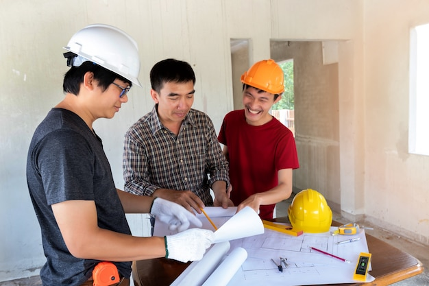Engineer and architect discussing with foreman in construction site.