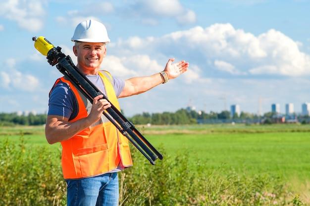 Инженер-архитектор-прораб на строительной площадке с измерительным прибором в руках.