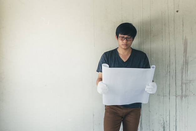 Engineer or architect holding blueprint in building construction site.