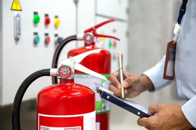 엔지니어는 화재 예방 실에서 안전 예방 및 화재 훈련을 위해 빨간색 소화기를 점검하고 검사합니다.