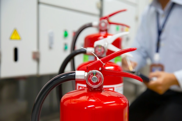 엔지니어는 화재 통제실에서 소화기를 검사합니다.