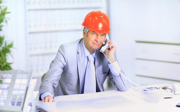 Инженер в возрасте разговаривает по телефону о планах чертежа.