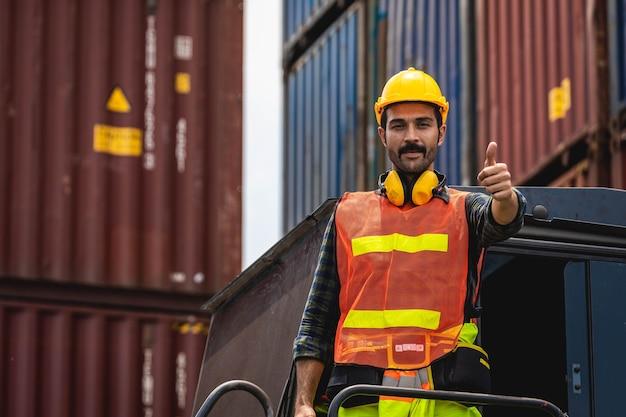 엔지니어 수염 남자는 노란색 헬멧을 도자기와 함께 서서 선적을 제어하고 조선소 또는 항구에서 수입 및 수출을 위해화물 화물선에서 컨테이너의 품질을 확인합니다.