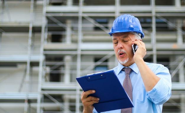 電話で話している建設現場でエンジニアビルダー