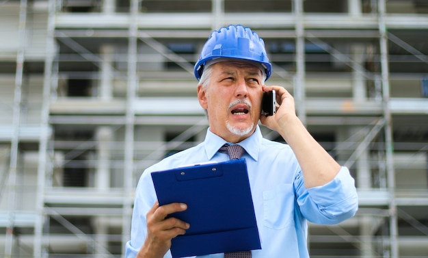 Engineer builder at construction site talking on the phone