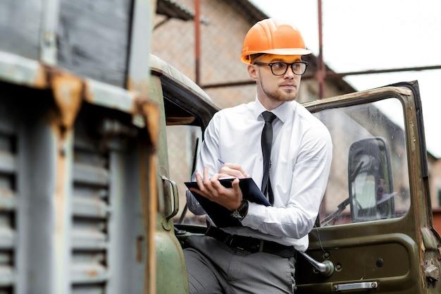 ヘルメットをかぶったエンジニアビルダーは、建設現場で図面を保持します