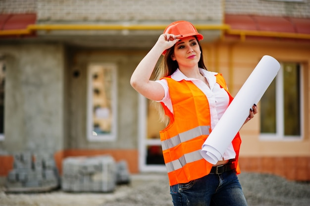 Engineer builder woman in uniform waistcoat and orange protective helmet hold business paper against new building