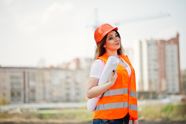 Engineer builder woman in uniform waistcoat and orange protective helmet hold business paper against new buildings with crane.