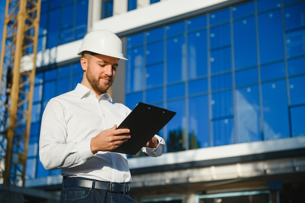 Engineer next to building cranes. concept - large construction project. architect directs the construction process. drawings and tablet in the hands.