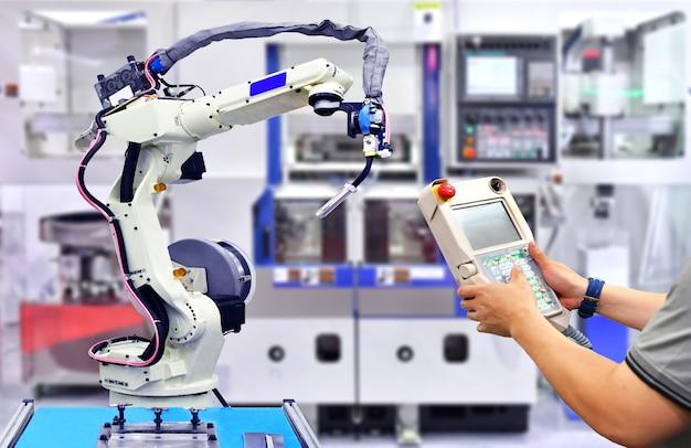 공장, 산업 로봇의 엔지니어 오렌지색 현대 로봇 시스템 점검 및 제어 자동화.