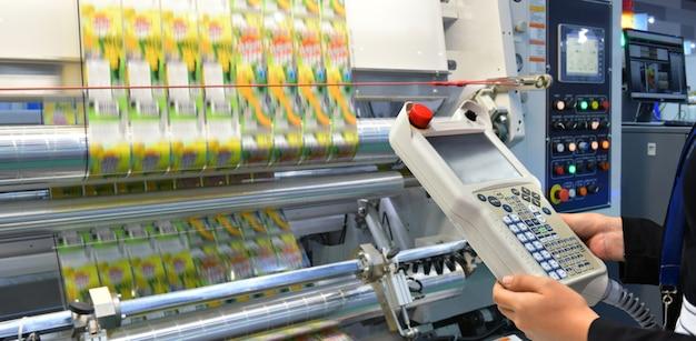 Инженер проверяет и контролирует автоматическую упаковочную машину высокотехнологичной пищевой упаковочной машины для промышленного