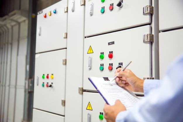 Инженер проверяет кнопку включения агрегата кондиционирования воздуха на панели управления.