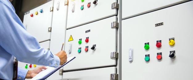 コントロールパネルシステムのエアハンドリングユニットahuスターターボタンをチェックするエンジニア。