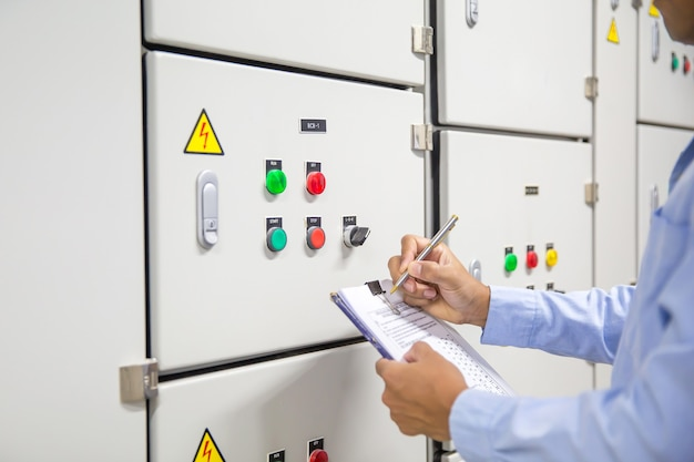 Engineer checking air handling unit ahu starter button at control panel system.