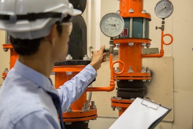 凝縮器ウォーターポンプと圧力計、圧力計付きチラーウォーターポンプをチェックするエンジニア。