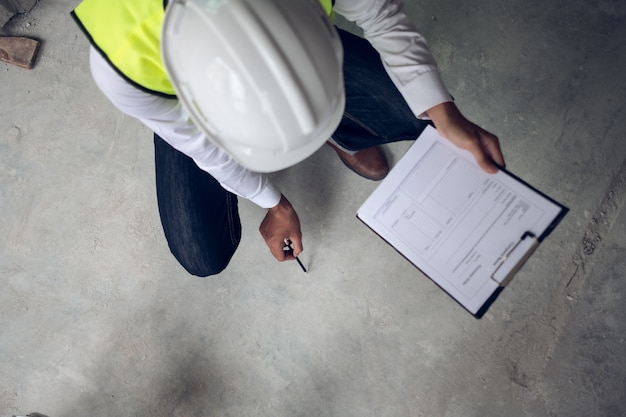 Engineer checking defect in construction site about surface of concrete floor