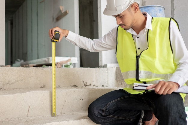 Engineer checking defect in construction site measures dimension of stair height