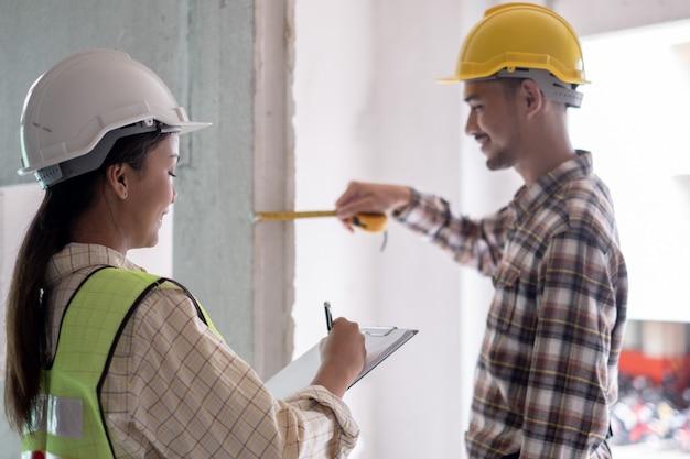 コンクリート柱の正しい寸法を測定する建設現場の欠陥をチェックするエンジニア