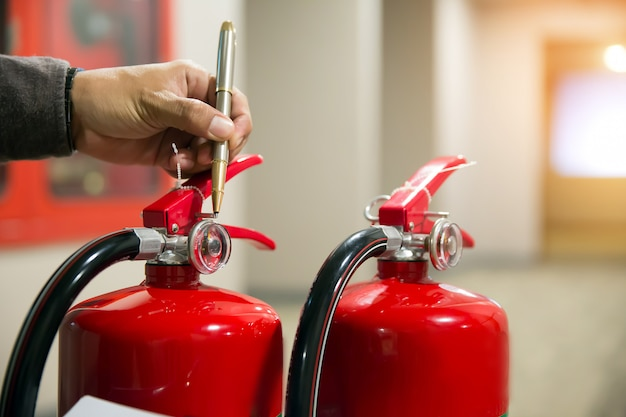 Engineer checking fire extinguisher